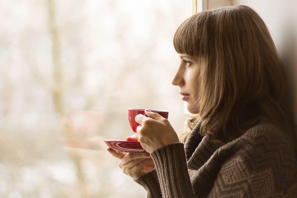 Belle fille buvant du café ou du thé près de la fenêtre